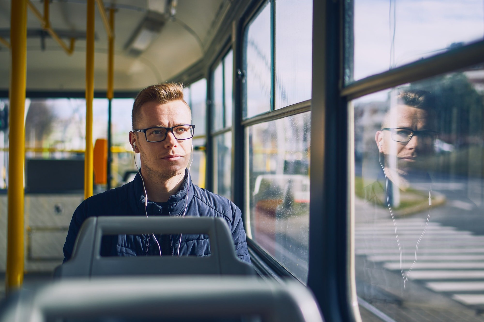 Young man listening music in tram. Travel by public transportation.